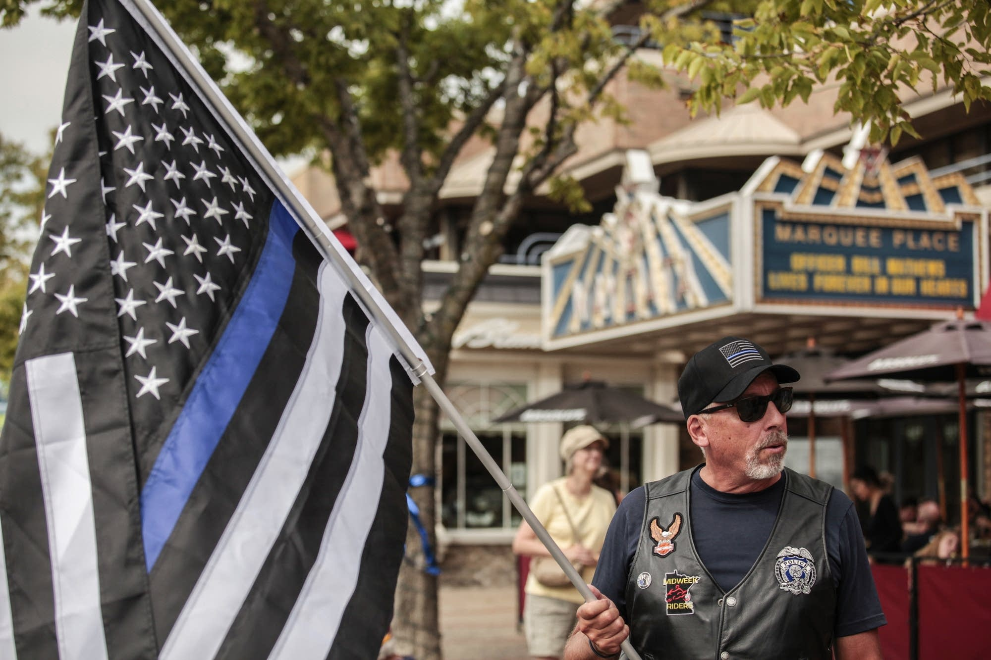 Retired officer Dennis Hansen holds a flag that represents police officers.
