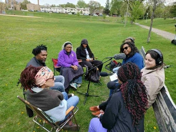 a group of people sitting in a park and talking