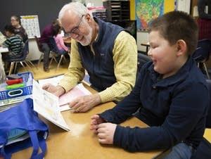Volunteer tutor Brooks Donald reads with kindergartner Bretton Larson.