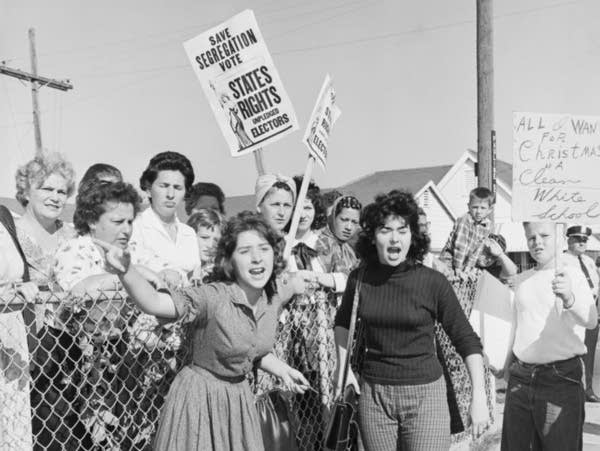 A black and white photo of protestors holding signs.