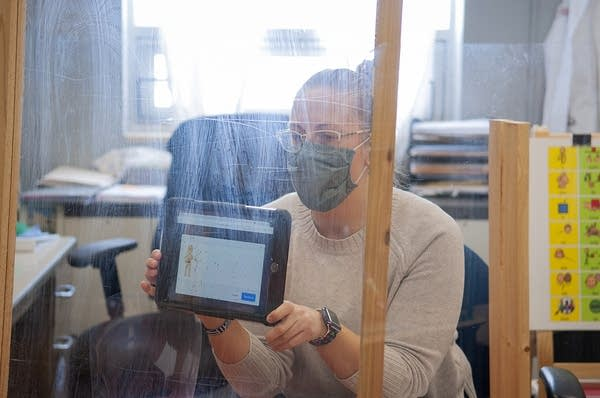 A speech-language pathologist sits behind a barrier while holding an iPad.