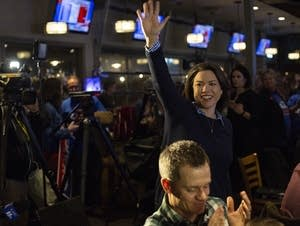 DFL Candidate Angie Craig waves as she enters her election party.
