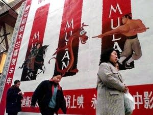 Pedestrians walk by an advertisement of the movie 'Mulan.'