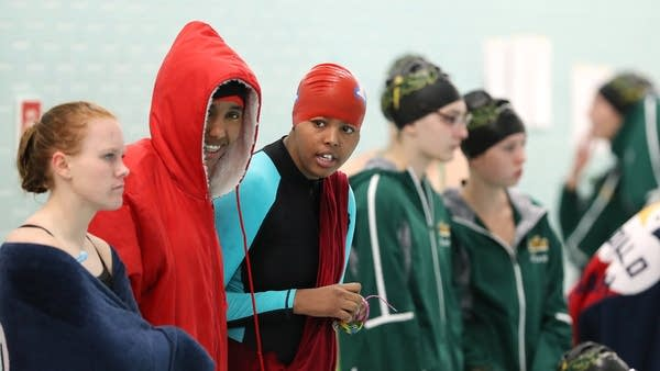 Nimo Gohe, in red jacket, and Suhan Mohamed cheer on their teammates.