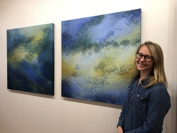 Annie Hejny stands next to two paintings hanging in her Minneapolis studio