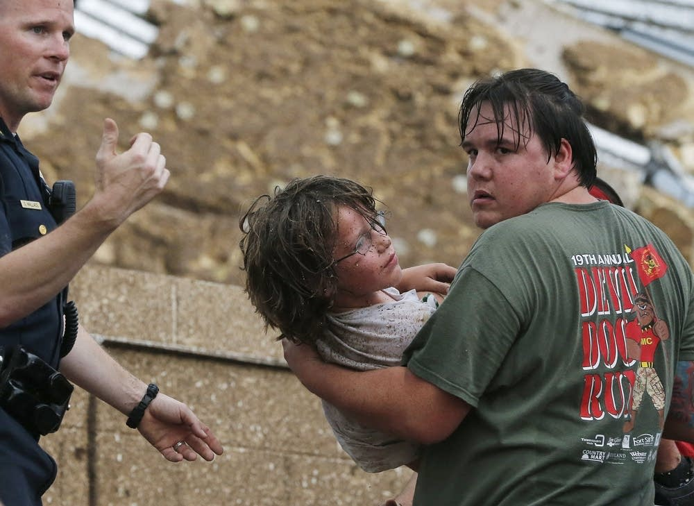 A child is carried from the rubble