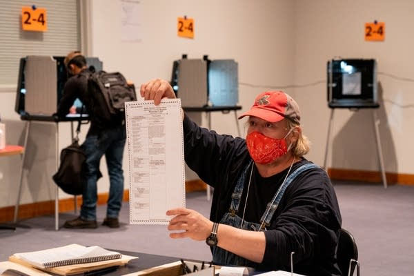 A man holds up a ballot.