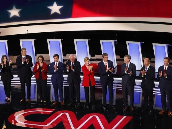 Ten Democrats stand together during presidential primary debate.
