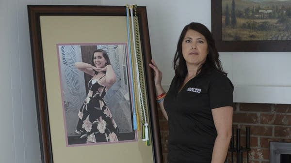 April Schentrup stands beside a photograph of her daughter.
