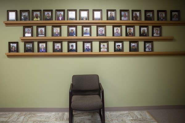 Framed photographs sit on a shelf on a green wall.