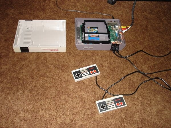 Nintendo NES game consul with top half taken off, on brown carpeting