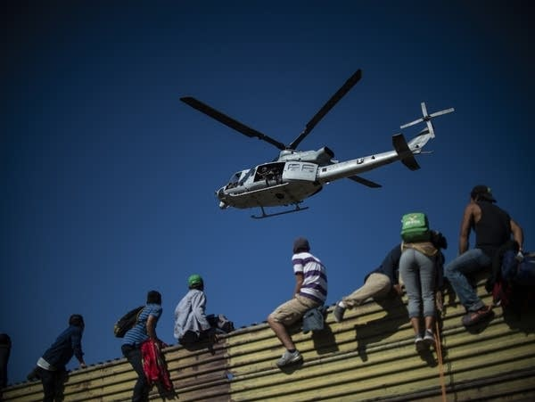 A group of Central American migrants climb the border fence