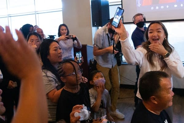 A family member holds up a cell phone with a screen view of Sunisa Lee