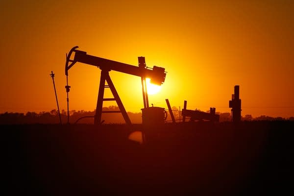 The sun sets behind an oil well