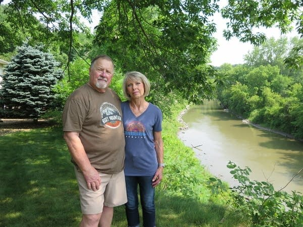 Two people stand by a river.
