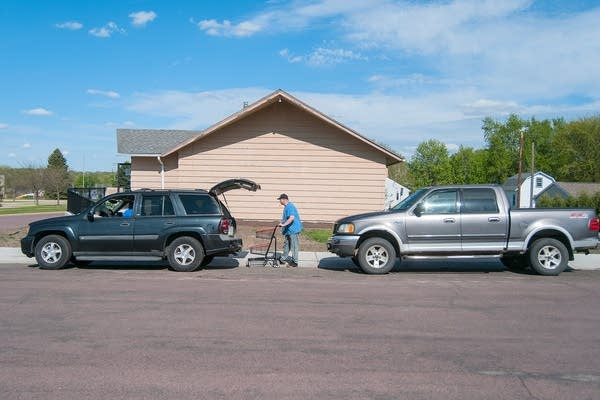 A person pushing a cart between a line of cars