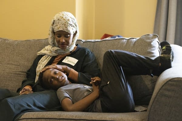 A woman sits on a couch with her son.