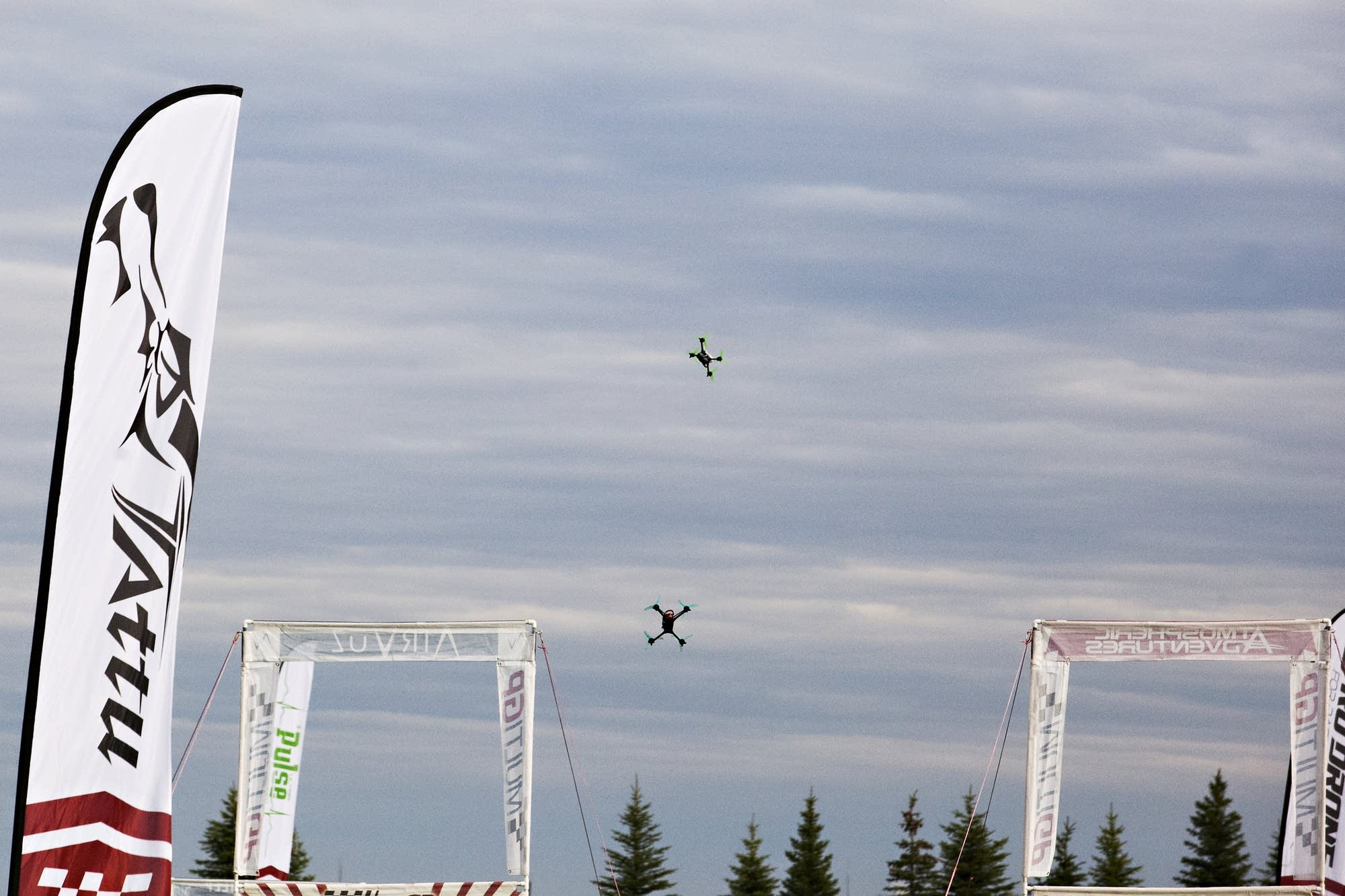 A pair of drones dot the sky during a race.