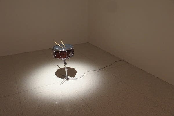 Pieces of art sit with a spotlight on them in a large, white room.