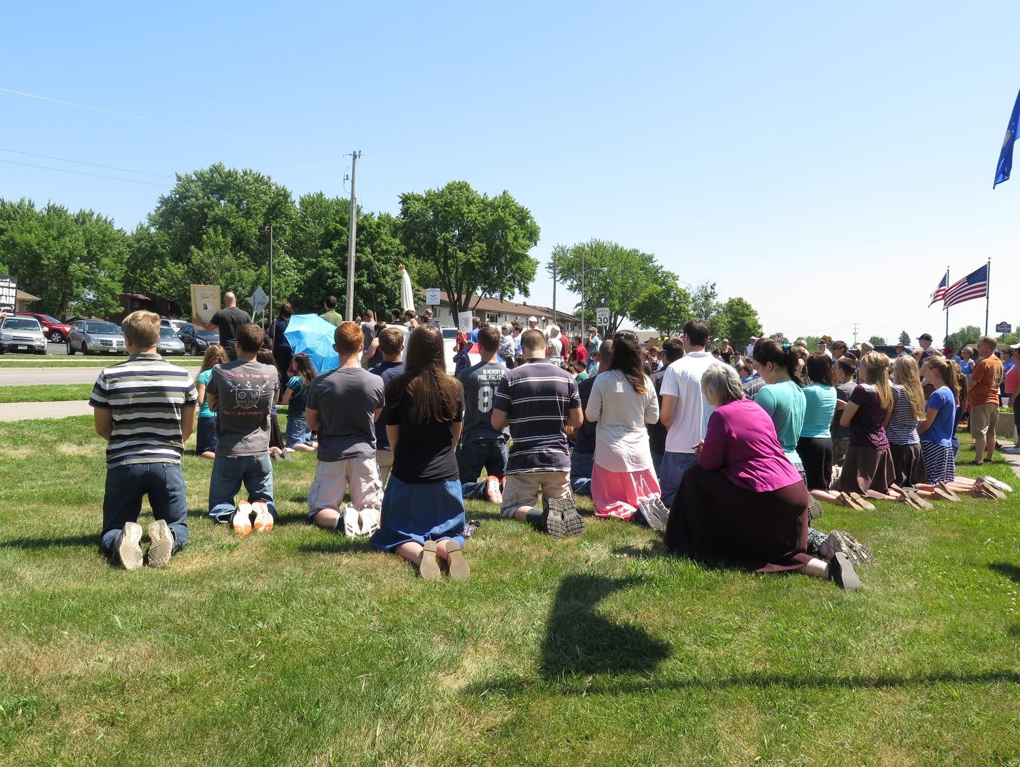 Protesters kneel to pray during a rally against a future satanic monument.