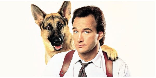 Jim Belushi with German Sheppard resting paw on his shoulder