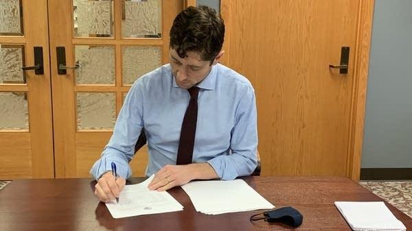 Minneapolis Mayor Jacob Frey signs the city's 2021 budget.