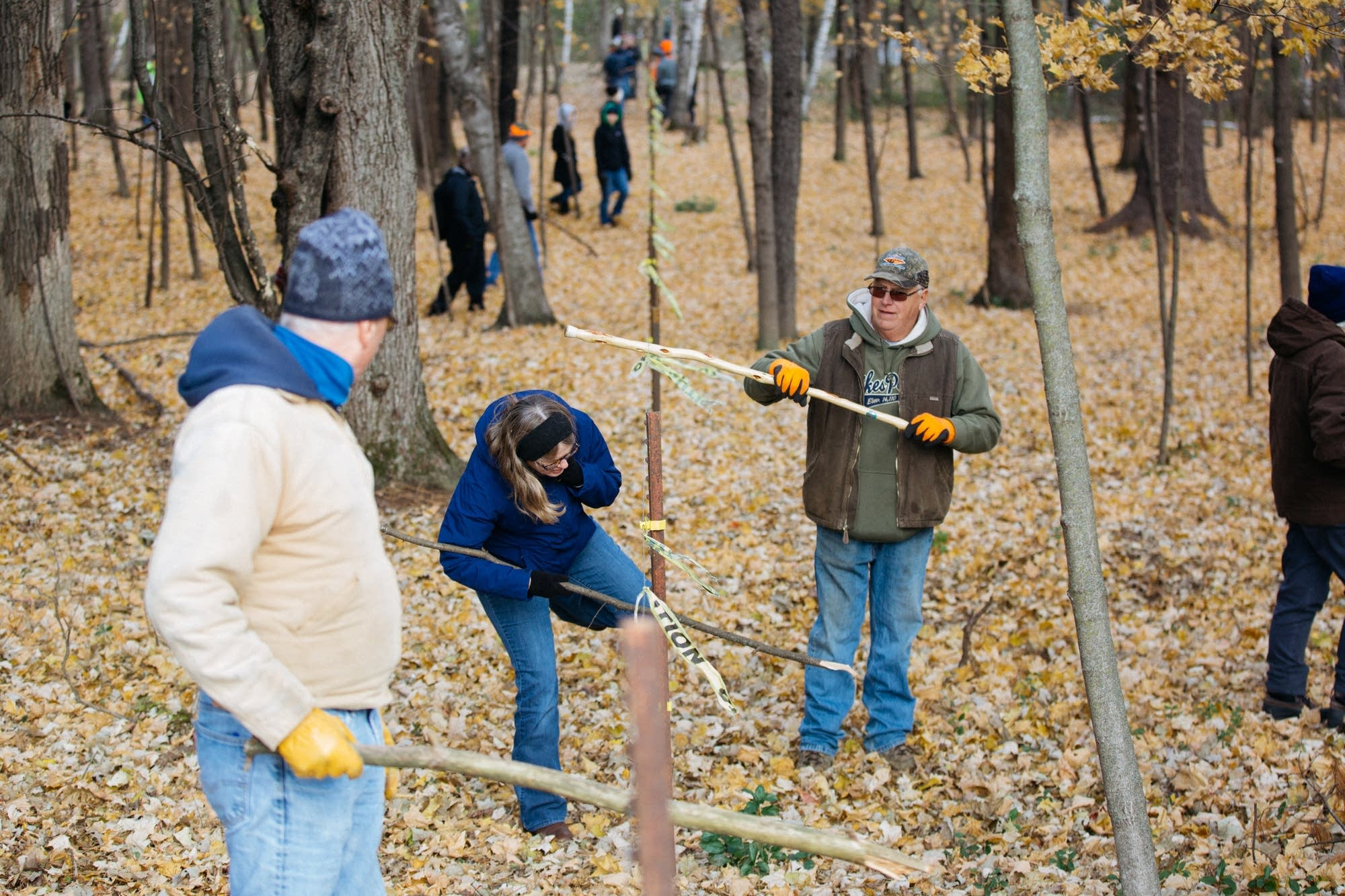 Volunteers use sticks and walking poles to help each other.