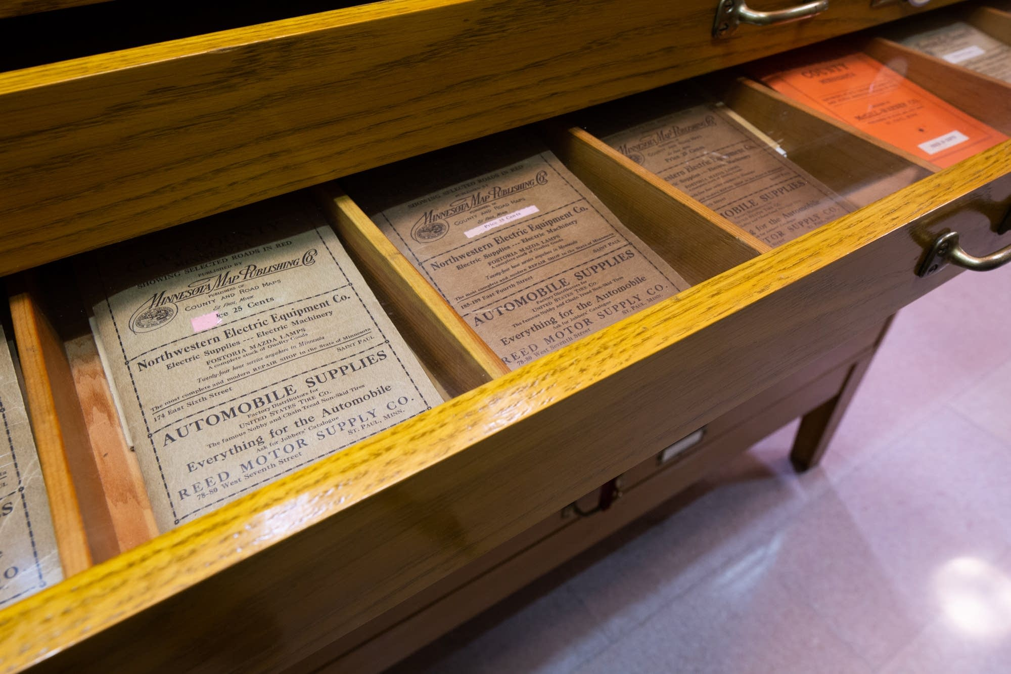 A drawer filled with historic road maps sits on display.