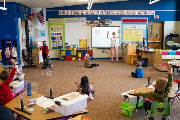 Kids in a classroom sit at their desks and on the floor.