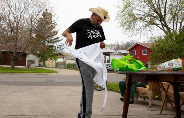 a man puts on an apron while standing in a driveway