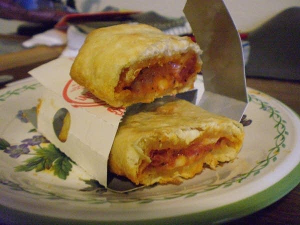 Pizza Hot Pocket (cooked) cut in half, stacked on a plate
