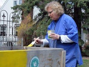 Moorhead Mayor Del Rae Williams paints her Little Free Garden.