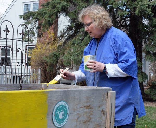 Moorhead Mayor Del Rae Williams paints her Little Free Garden.