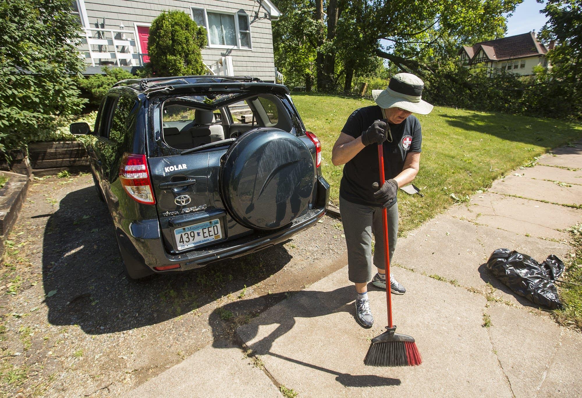 Alison Lutterman sweeps glass off the sidewalk