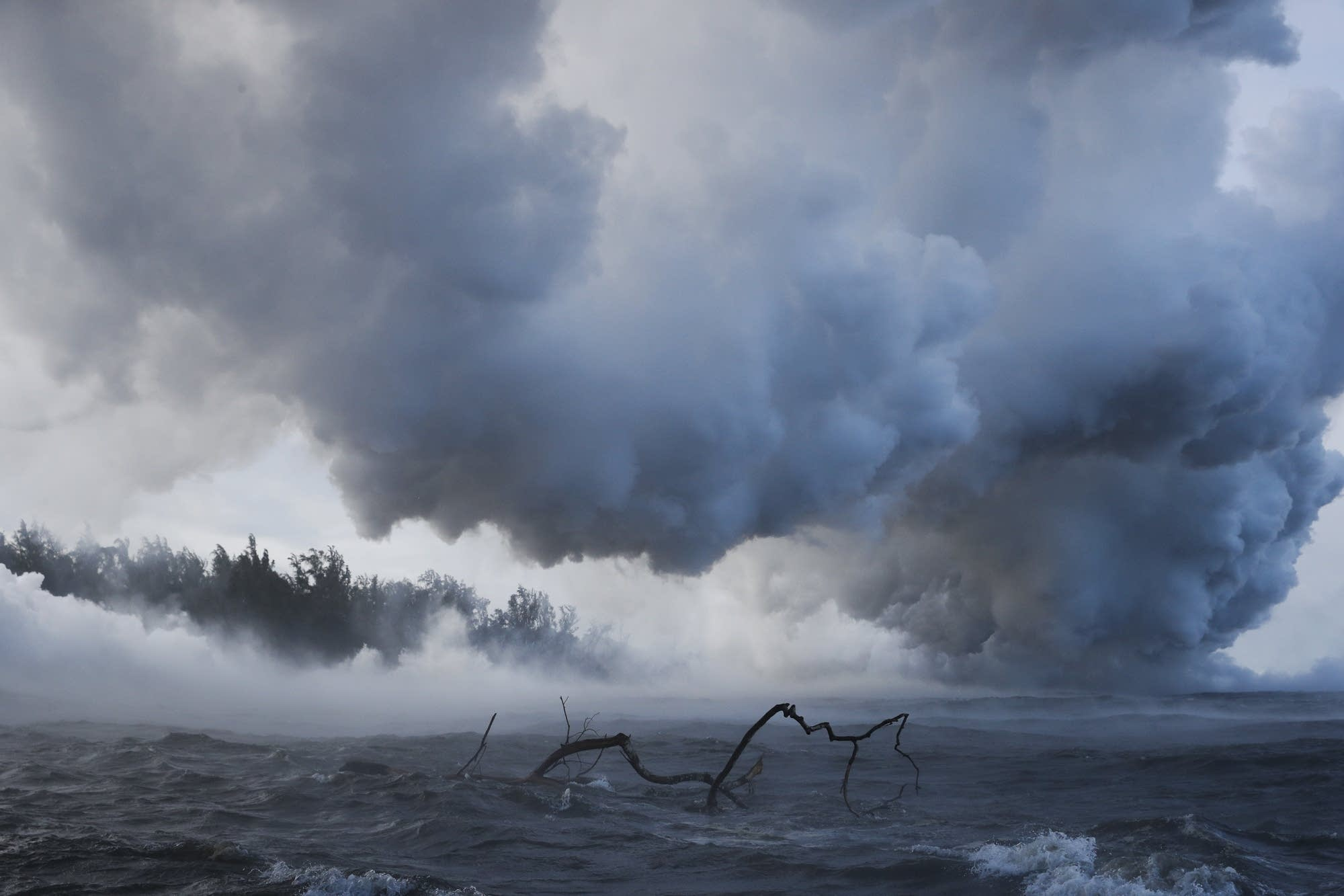 Plumes of steam rise as lava enters the ocean near Pahoa, Hawaii.