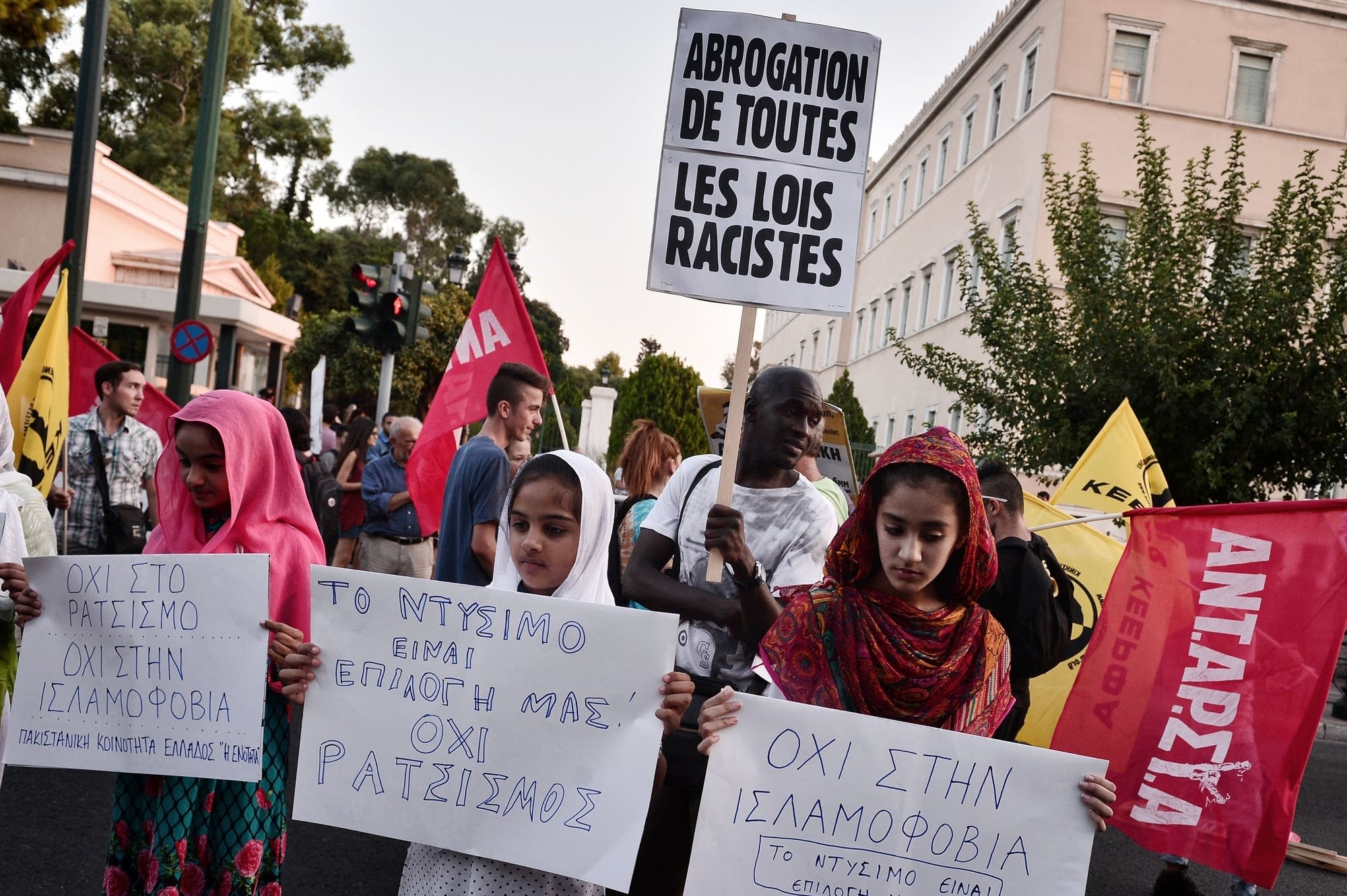 Muslim migrant girls hold placards reading 'No to Islamophobia'