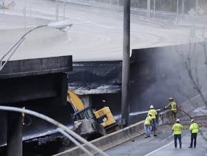 Crews work on a section of an overpass that collapsed from a large fire