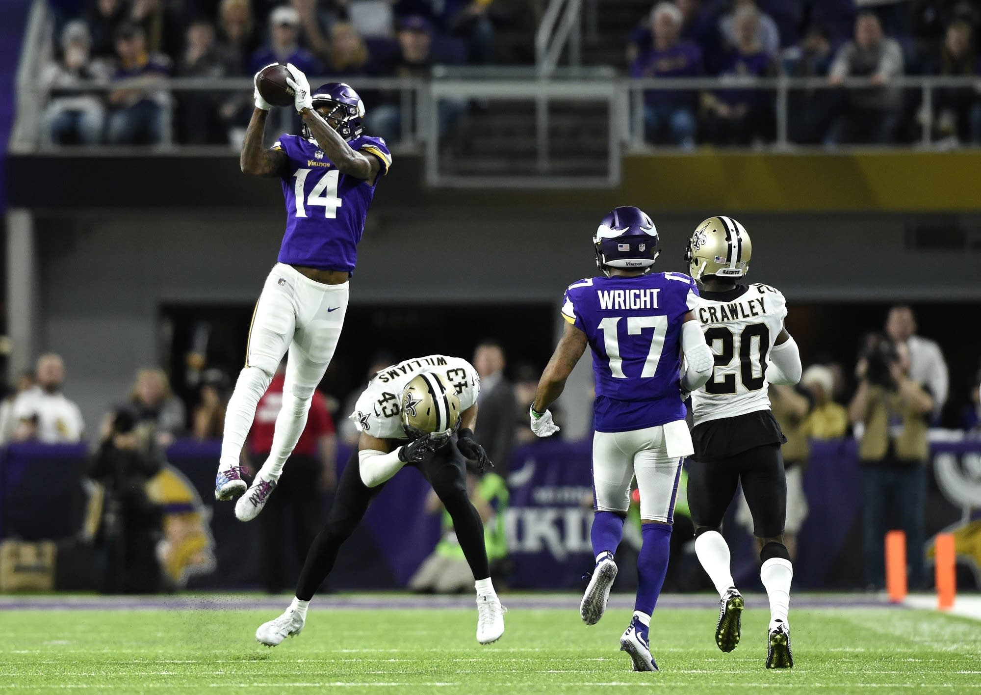 Stefon Diggs (#14) of the Minnesota Vikings leaps to catch the ball.