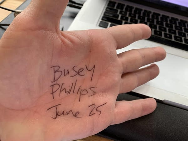 "The palm of a white man's hand w/ ""Busey Phillips June 25th"" written on it"