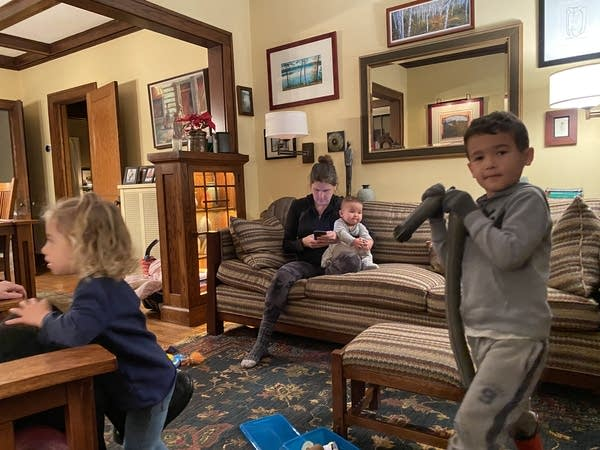 A woman texts on a couch while two children play in front of her.