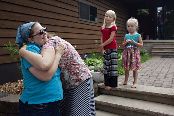 Two women embrace outside a home as two girls stand on