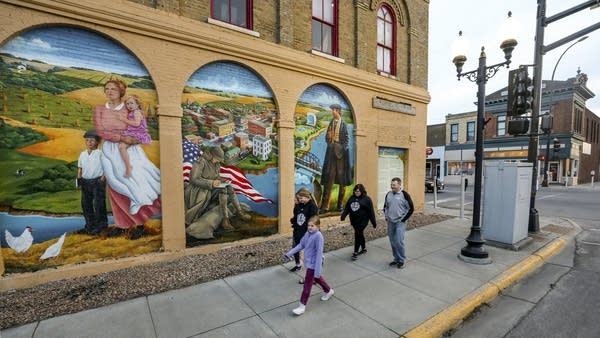 A family walks past a mural depicting the history of Sauk Centre.
