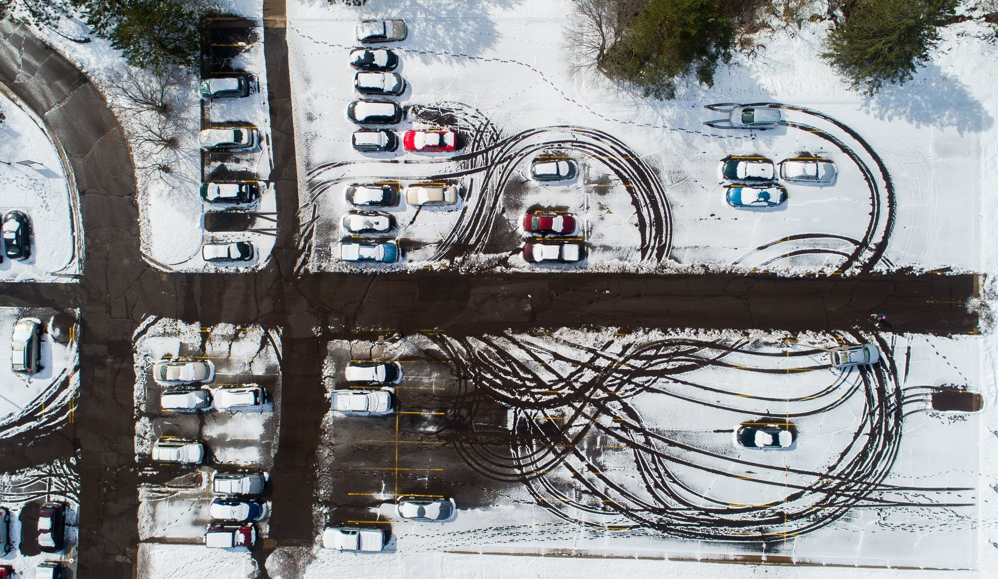 Vehicles, people leave patterns in a snowy parking lot.