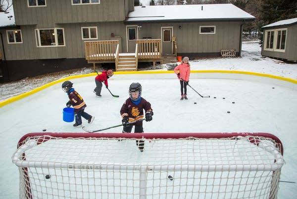 Children skate on a backyard hockey rink.