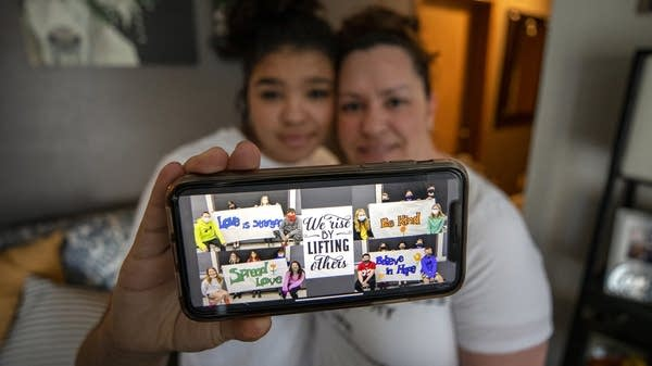 A picture displayed on a cellphone is held up by a student and her mother.