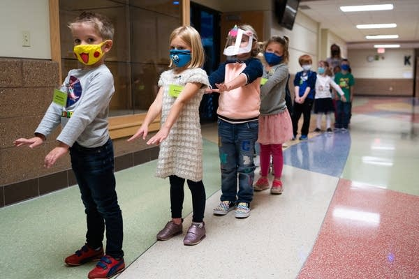 Students in masks walk in a line with their arms out in front of them.