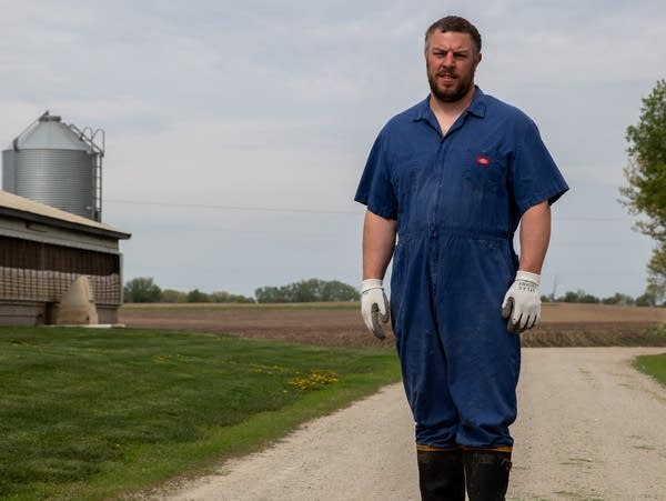 A man stands on a gravel road in coveralls.
