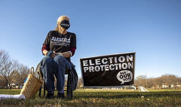 "A person sitting in a chair beside a sign that reads ""election protection"""