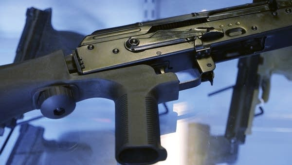 A device called a 'bump stock' is attached to a semi-automatic rifle.