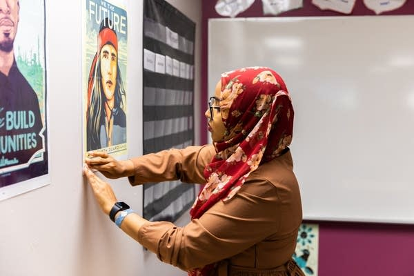Qorsho Hassan puts a poster on the wall of her new fourth grade classroom.